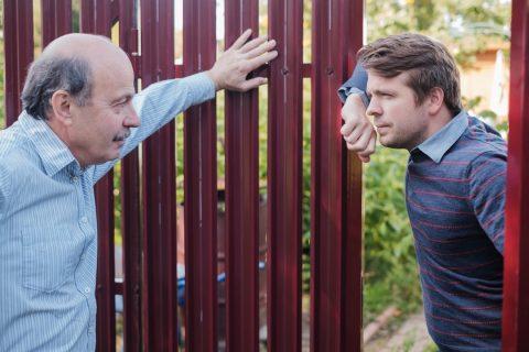 Voisins discutant à coté d'une clôture